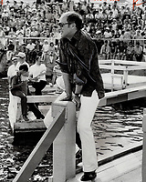 1969 FILE PHOTO - ARCHIVES -<br /> <br /> Down on a pier with Pierre. Prime Minister Pierre Trudeau dangles his legs over floating platform's guardrails after finishing impromptu jig for a crowd in Quebec's Lac St. Jean region Saturday.<br /> <br /> 1969<br /> <br /> PHOTO : Boris Spremo - Toronto Star Archives - AQP