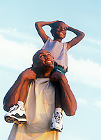 Boy gets a ride on his fathers shoulders.