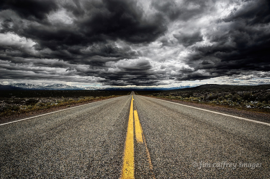 Storm clouds hover over US highway 64 as it crosses the Taos Plateau west of the town of Taos in north-central New Mexico.