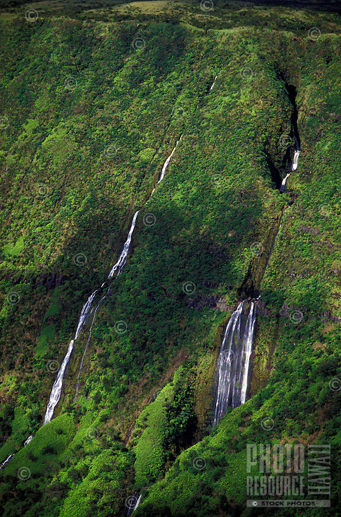 A lush, green valley wall streaked with waterfalls and partly shaded by cloud shadows in Kohala, the north coastal area of the Big Island