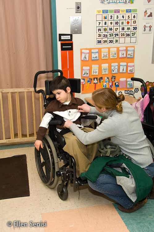 MR / Albany, NY.Langan School at Center for Disability Services .Ungraded private school which serves individuals with multiple disabilities.Teaching assistant talks to student, while fixing his shirt after removing his coat at arrival time. Boy: 8, cerebral palsy, spastic quadriplegic, nonverbal with expressive and receptive language delays.MR: Neu1, Hac2.© Ellen B. Senisi