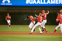 Jordyn Adams (3) of Green Hope High School in Cary, North Carolina is doused with water by teammates Blaze Alexander (21) of Bishop Verot High School in Cape Coral, Florida and Ethan Hankins (31) of Forsyth Central High School in Cumming, Georgia after hitting a walk off single during the Under Armour All-American Game presented by Baseball Factory on July 29, 2017 at Wrigley Field in Chicago, Illinois.  (Mike Janes/Four Seam Images)