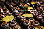Workers make soy sauce surrounded by hundreds of jars filled with fermenting rice and soy beans using a 'secret' age old recipe that has been passed down by generations in Vietnam.   Famously named 'Ban' soy sauce, after the village in the Hung Yen province, its 'secret' partly comes from the use of rainwater or water from a borewell to wash and soak the rice. <br /> <br /> The rice is then cooked so it becomes sticky before it is scattered onto a large, bamboo flat basket and dried in an airy place until it turns yellow.  SEE OUR COPY FOR DETAILS.<br /> <br /> Please byline: Nguyen Phuoc Hoai/Solent News<br /> <br /> © Nguyen Phuoc Hoai/Solent News & Photo Agency<br /> UK +44 (0) 2380 458800
