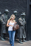 A young woman holding her handbag smiles as she steps away from a sculpture depicting the poverty of the great depression. The sculpture is part of the FDR memorial in Washington DC.