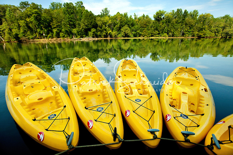 A group of bright yellow kayaks sit on the water waiting for kayakers at the U.S. National Whitewater Center in Charlotte, NC. The USNWC is a non-profit outdoor recreation center on 400 acres adjacent to the Catawba River. The whitewater center is an athletic training facility for whitewater rafting and whitewater slalom racing, kayaking, canoeing, rock climbing, mountain biking and hiking. The primary feature of the USNWC is the world's largest and most-complex recirculating artificial whitewater river, which was designed by Scott Shipley, a three-time Olympian.