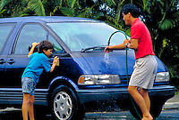 Japanese American father and son washing car together.