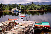 Cape Breton, Nova Scotia, NS, Canada, Red and blue lobster boats in Dingwall in Cape Breton. Lobster traps on dock.