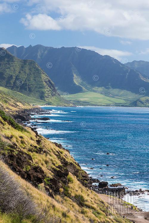 Hikers on the Ka'ena Point Trail and coastline, with Yokohama Bay and Makua Valley in the background, West O'ahu.