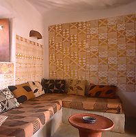 A simple seating area in the Hotel Djenne Djenno Cushions covered in traditional Bogolan pattern covers are placed on a mud corner seat. The Bogolan pattern is continued on the painted wall behind.