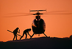 Heliskiers boarding helicopter at sunset. Mount Hutt. Canterbury New Zealand.