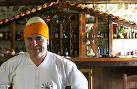 UNK UNK the owner of the restaurant in traditional clothing and Albanian hat, white with round top tied with an orange yellow cloth. It is said that it the round top of the hat is pointing up and is round then the country is free, if the top of the hat is indented pressed down then the country is oppressed. Tradita traditional restaurant, Shkodra. Albania, Balkan, Europe.