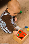 13 month old toddler boy sitting playing with geometric shape sorter toy, fitting block in square hole