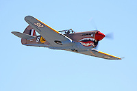 """John Curtiss Paul pilots the P-40E Warhawk """"Sneak Attack"""" during the Unlimited Bronze Class Finals at the 2009 National Championship Air Races. Race 18 finished third in the class with a speed of 324.704 mph."""
