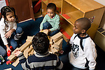 Preschool Headstart New York City 4 year olds group of girls and boys building together talking to negotiate how to proceed horizotnal