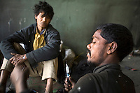 Homeless addicts prepare and inject heroin under a flyover, New Delhi.