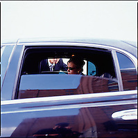 Man looking through limousine window at woman executive inside<br />
