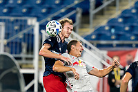 FOXBOROUGH, MA - AUGUST 29: Henry Kessler #4 of New England Revolution and Tom Barlow #74 of New York Red Bulls battle for head ball during a game between New York Red Bulls and New England Revolution at Gillette Stadium on August 29, 2020 in Foxborough, Massachusetts.