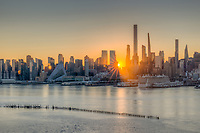 The rising sun shines through the buildings of the Manhattan West Side skyline in New York City as viewed over the Hudson River looking east from New Jersey.