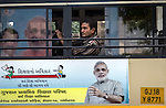 13 September, 2013, Ahmedabad, Gujarat INDIA :  A man looks out of a bus in Ahmedabad  featuring a poster of Chief Minister of Gujarat , Narendra Modi.   Mr. Modi has been announced as the Prime Ministerial candidate for the opposition BJP party in the Indian general elections slated for 2014.   Mr.Modi has been a controversial figure since his involvement in the 2002 Gujarat riots where a train full of Hindu pilgrims was attacked by Muslims returning from a disputed temple site in Ayodhya.  In retaliation some estimate up to 2000 Muslims lost their lives in communal violence.   Mr. Modi is alleged to have condoned the violence despite being cleared of any allegations by a Special Investigation Team (SIT) appointed by the Supreme Court of India. Picture by Graham Crouch/New York Times