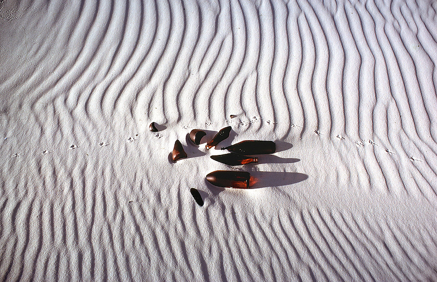Bird tracks and left over Beer Bottles in the sand dune on Frazer island Queensland Australi, leaving rubbish behind