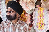 India, Dehradun.  Sikh Shopowner Selling Garlands of Rupee Banknotes as Wedding Gifts for Brides.