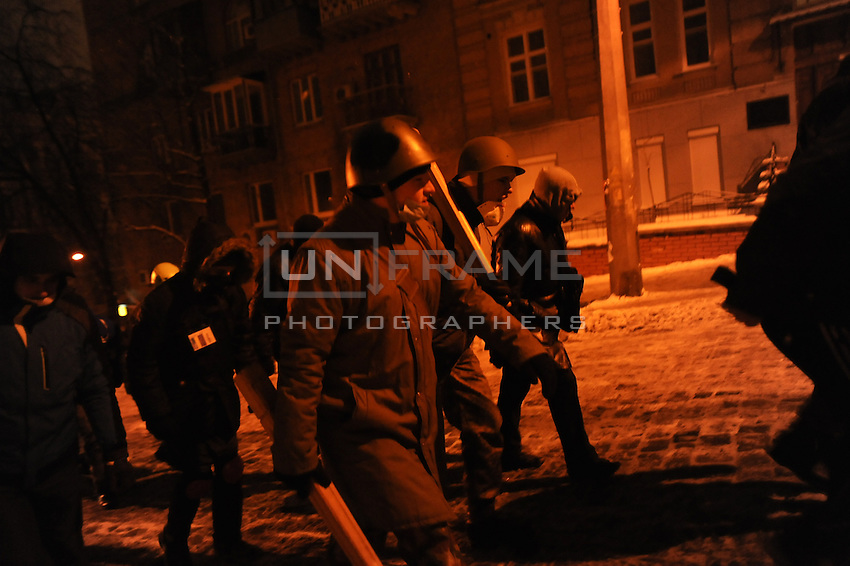 Armed group of protesters heading to protect barricades in the government district. Kiev. Ukraine