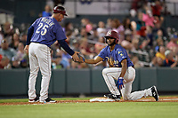 Frisco RoughRiders manager Joe Mikulik (25) high fives Franklin Rollin (57) during a Texas League game against the Springfield Cardinals on May 4, 2019 at Dr Pepper Ballpark in Frisco, Texas.  (Mike Augustin/Four Seam Images)