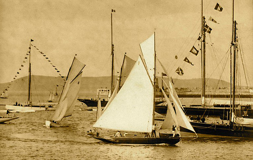 The Dublin Bay 25 Fodhla winning a Kingstown Regatta in 1900 after threading her way to the finish through an intriguing anchored selection of large Victorian yachts.