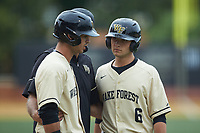 Michael Turconi (6) and Patrick Frick (5) get instructions from Wake Forest Demon Deacons head coach Tom Walter (16) during the game against the Miami Hurricanes at David F. Couch Ballpark on May 11, 2019 in  Winston-Salem, North Carolina. The Hurricanes defeated the Demon Deacons 8-4. (Brian Westerholt/Four Seam Images)
