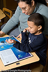 Educaton preschool 4-5 year olds female teacher looking at book with boy talking language development vertical