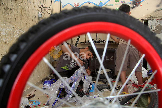 Khamis al-Burdini, 15, a Palestinian youth repairs bicycles at his workshop in Gaza city, on March 13, 2013. al-Burdini opened his workshop 3 years ago after leaving his school to provide his poor family . Photo by Ezz al-Zanoon