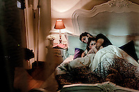 Two actors, playing lovers, lie together in a bed on a set during filming of 'Revenge'.