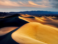 First light on sand dunes with clouds. Death Valley National Park, California. Sky has been added