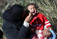 Pictured: A young mother tries to feed her young child on the hard shoulder in Tempe Thursday 25 February 2016<br />Re: Hundreds of migrants, including families with young children, that were stranded at Tempe in central Greece, were forced to walk on foot on the motorway to reach Idomen, about 168 kilometres away, in the northern part of the country, at the Greek FYRO Macedonian border. Local police were at first escorting them, then made sure that they were safely transported on coaches.