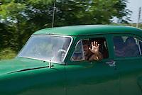 Classic American car driving on the highway between Havana and Pinar del Rio, Cuba.