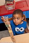 Education Preschool 3 year olds boy building block tower with wooden alphabet blocks