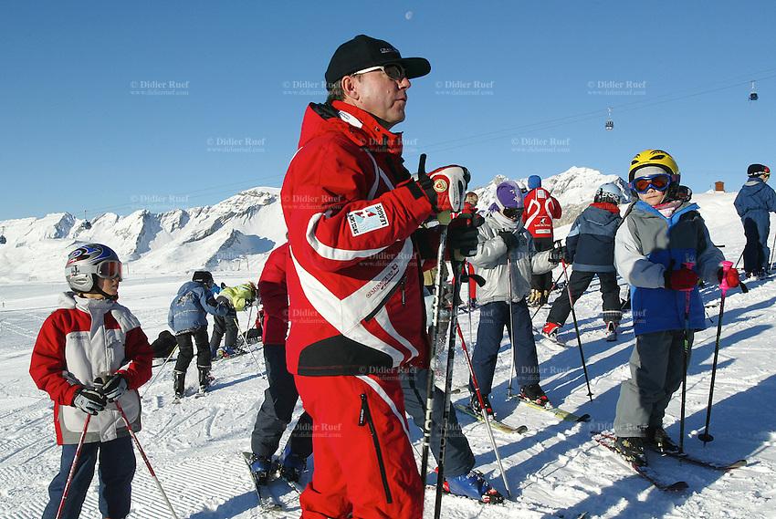 Switzerland. Valais. Crans Montana. Winter ski resort. Swiss Ski School teacher meet his students skiers before the start of the class. Blue sky on a sunny day. © 2005 Didier Ruef
