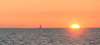 A sailboat sails into the setting sun in the Gulf of Bothnia near the Norrskär Island group.