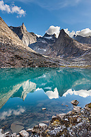 Dramatic granite spires of the Arrigetch Peaks reflect in the mirror calm mountain lake, Gates of the Arctic National Park, Alaska.