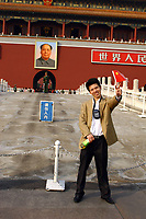 CHINA. Beijing.  A man stands in front of the famous Mao Zedong portrait that hangs on the 'Gate of Heavenly Peace' which leads into the Forbidden City and is opposite Tiananmen Square. Mao is still revered in China even 30 years after his death and 40 years since the end of the 'Cultural Revolution' and the 'Great Leap Forward' where it is alleged he was responsible for the death of some 20 million Chinese people. Nevertheless, every day thousands of Chinese people make the pilgrimage to stand and have their photo taken in front of his most famous portrait. 2005.