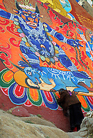 Tibetan Buddhist pilgrim prays at a rock painting of blue protector deity Yama Dharmaraja with crown of skulls, garland of severed heads and standing on buffalo and human corpse, on the sacred circuit, or kora, around the monastery walls of Sera Monastery, Lhasa, Tibet, China.
