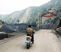 A man travels on a motor cycle as he enters a coal mining site.