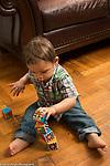 18 month old toddler boy stacking blocks into tower