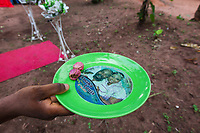 """Nigeria. Enugu State. Awhun. Igbo traditional wedding ceremony. Two kola nuts on a green plastic plate with a smiling couple ( Amaka and Louis) who got married on 23th February 2013. The kola nut is the fruit of the kola tree, a genus (Cola) of trees that are native to the tropical rainforests of Africa. The caffeine-containing fruit of the tree is used as a flavoring ingredient in beverages, and is the origin of the term """"cola"""". 29.06.19 © 2019 Didier Ruef"""