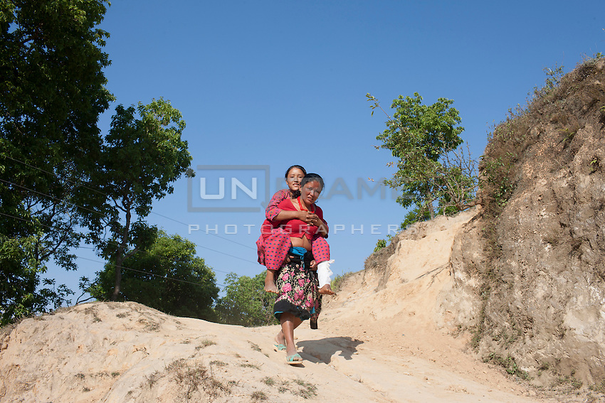 A mother carries her injured daughter Nikita,14, on her back. Outside of Kathmandu, Nepal. May 05, 2015