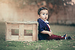 A little boy with a look surprised on his face sits on grass. Photo by Sanad Ltefa