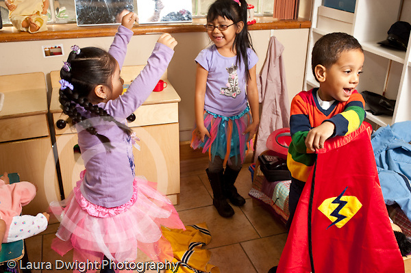 Education preschool pretend play girls playing in dressup ballerina outfits boy holding out superhero cloak he is about to put on
