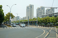 Suzhou, Jiangsu, China.  Street Traffic and High-rise Apartment Buildings.
