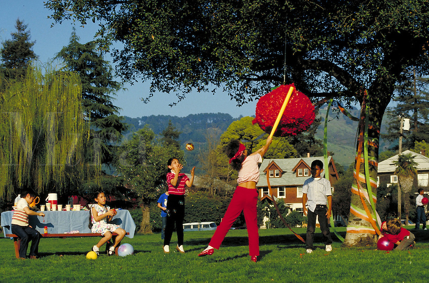 HISPANIC BOY AND FRIENDS WITH TOMATO PINATA PARTY. HISPANIC BOY AND FRIENDS. SAN FRANCISCO CALIFORNIA USA.