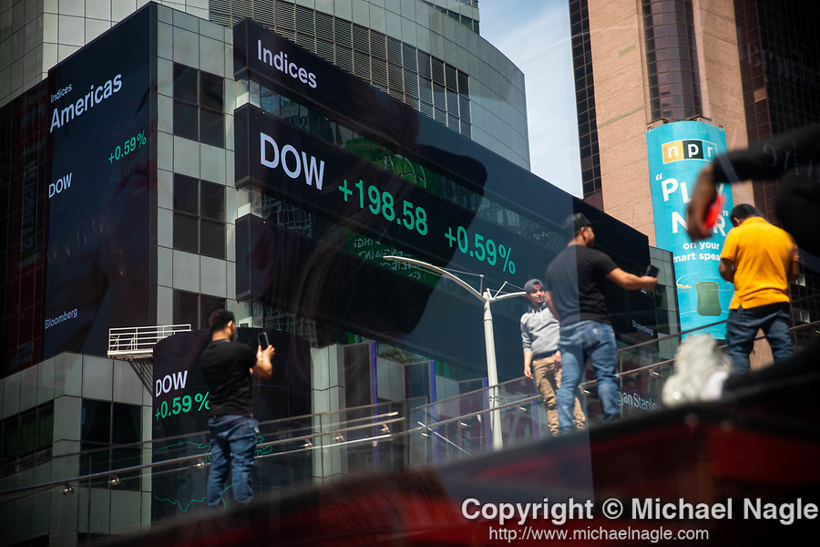 Dow Jones Industrial Average (DOW) information is displayed on monitors in front of Morgan Stanley in New York on Wednesday, April 14, 2021. Photographer: Michael Nagle
